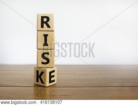 Risk Vs Rise Symbol. Turned A Wooden Cube And Changed The Word Risk To Rise. Beautiful Wooden Table,