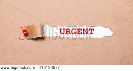 Beneath The Torn Strip Of Kraft Paper Attached With A Red Button Is A White Paper Labeled Urgent