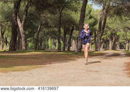 Sporty Mature Woman Running In The Park In Beautiful Nature. Healthy And Sporty Lifestyle Concept.