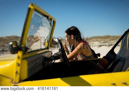 Happy caucasian woman leaning against beach buggy by the sea putting on lipstick. beach break on summer holiday road trip.