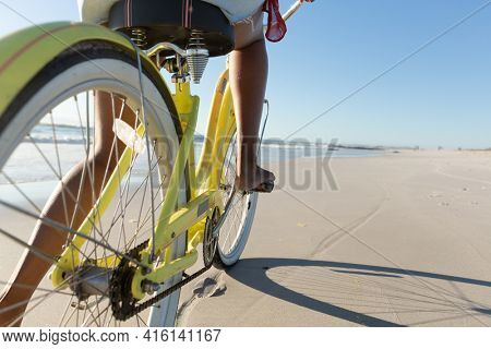 Low section of mixed race woman on beach holiday riding bicycle on the sand by the sea. outdoor leisure vacation time by the sea.