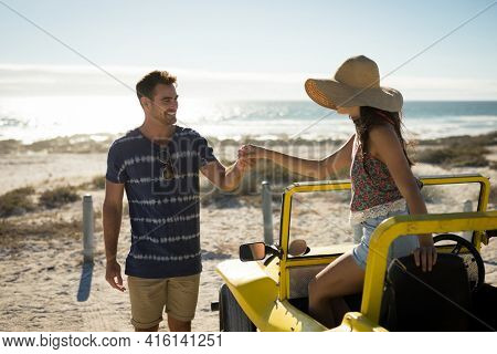 Happy caucasian couple on the beach assistance in getting out of the beach buggy. beach break on summer holiday road trip.