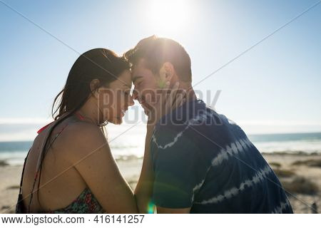 Happy caucasian couple on the beach touching foreheads. love, romance and beach break summer holiday.