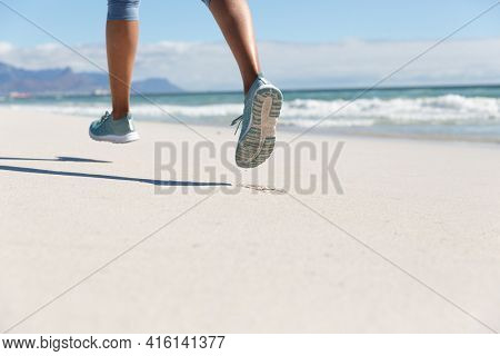 Low section of mixed race woman exercising on beach running. healthy outdoor leisure time by the sea.
