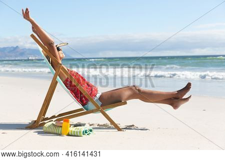 Mixed race happy woman on beach holiday sitting in deckchair stretching. healthy outdoor leisure time by the sea.