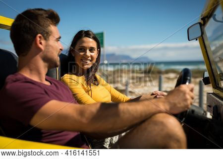 Happy caucasian couple sitting in beach buggy by the sea talking. beach break on summer holiday road trip.