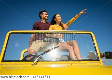 Happy caucasian couple sitting in beach buggy by the sea pointing. beach break on summer holiday road trip.