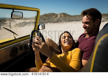 Caucasian couple lying on a beach buggy by the sea using smartphone. beach break on summer holiday road trip.