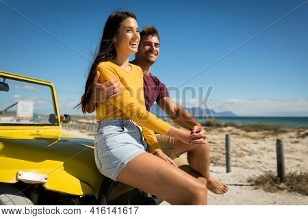 Happy caucasian couple sitting on beach buggy by the sea holding hands. beach break on summer holiday road trip.