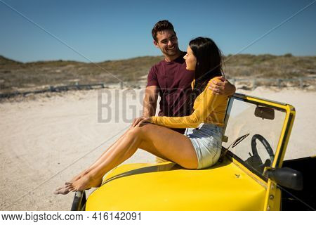 Happy caucasian couple by the sea smiling to each other, woman sitting on beach buggy. beach break on summer holiday road trip.