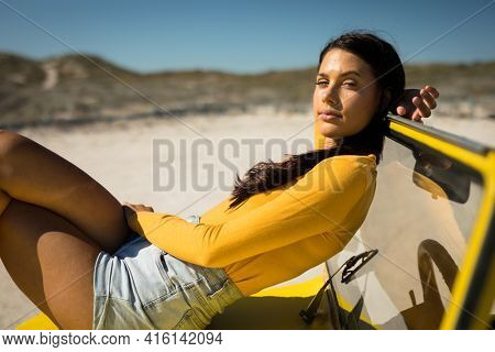 Caucasian woman lying on a beach buggy looking to camera. beach break on summer holiday road trip.