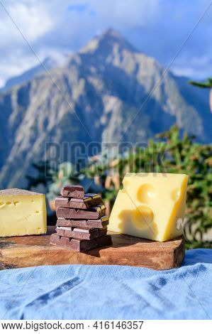 Tasty Swiss Cheeses And Dark Pure Chocolate, Emmental, Gruyere, Appenzeller Served Outdoor With Alpi