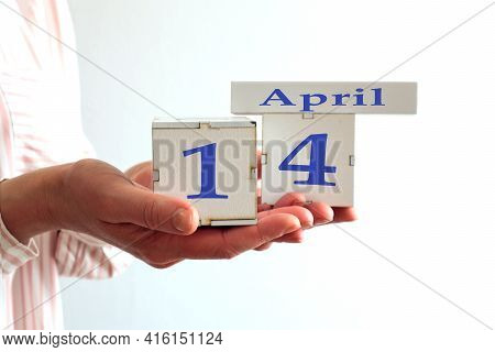Calendar For April 14 : Women's Hands Hold Cubes With The Number 14, The Name Of The Month Of April