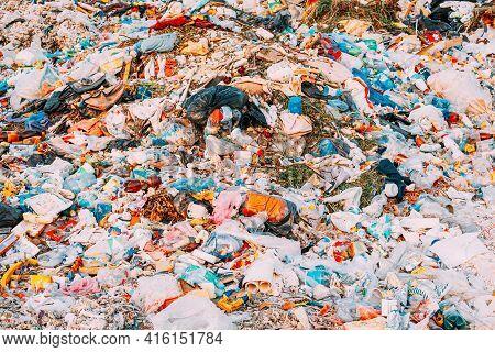 Pile Of Domestic Garbage Background. Large Heap Of Garbage. No Logo. Used Bags , Broken Bottles Dirt
