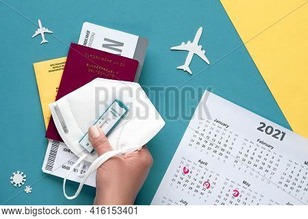 New Normal Travel During Covid-19 Restrictions, Flat Lay On Green And Yellow Paper. Hand Hold German