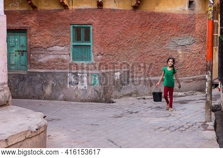 Jodhpur, India, March 21 2017: Young Girl Carrying Water In The Streets Of The Blue City Of Jodhpur