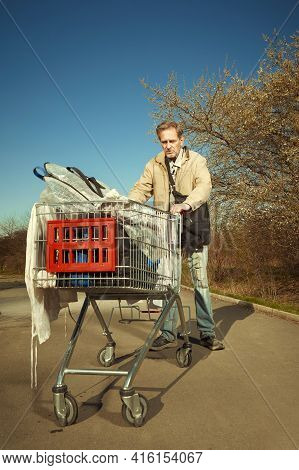 Older Beggar Man With His Property In Shopping Cart On Sidewalk