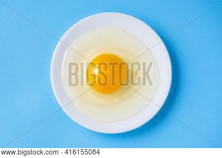Raw Egg On A White Plate. View From Above. Fresh Egg With A Bright Yolk On A Blue Background.