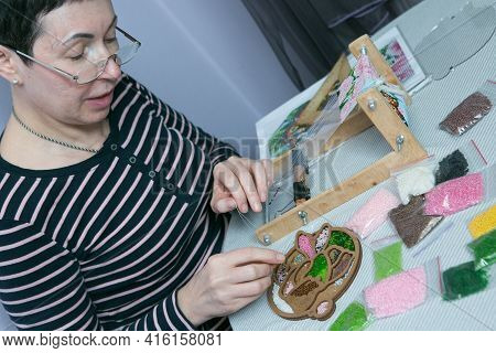 Weaving From Beads. A Beautiful Middle-aged Woman Is Engaged In Her Favorite Pastime.