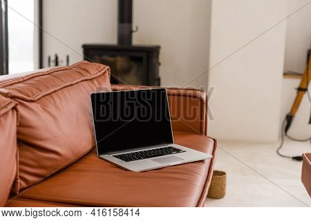 Laptop With Blank Screen On Sofa In Livingroom
