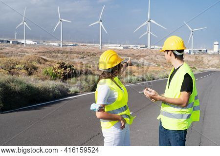 Wind Energy Concept, Two Engineers Standing In Front Wind Energy Mills Farm And Showing At It, Eco F