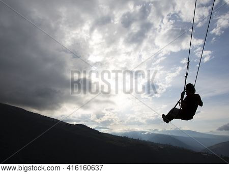 Banos, Ecuador - 21/02/2015: Silhouette Of Happy Young Man On A Swing With A Fantastic Mountain View