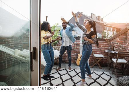 Multi Ethnic Group Of Friends Dancing And Relaxing On Rooftop. Group Young Hipsters Drinking Alcohol