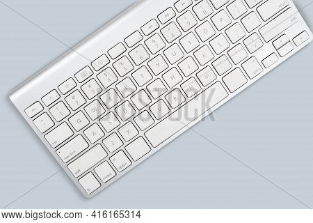 White Computer Keyboard On Sky Grey Background With Copy Space