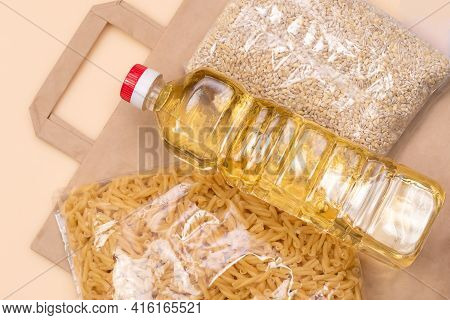 Paper Bag With Food Supplies Crisis Food Supply On A Light Yellow Background. Pearl Barley, Pasta, S