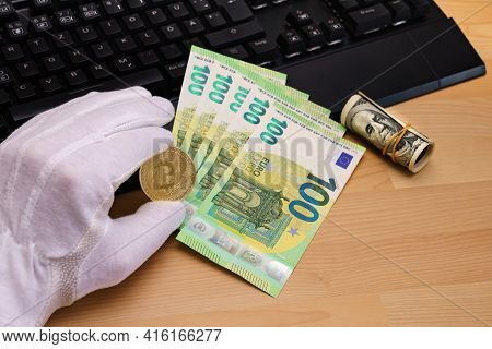A Hand In A White Glove Holds A Bitcoin. Near A Roll Of One Hundred Dollars. Pc Keyboard And One Hun