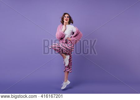 Full-length Shot Of Laughing Wonderful Girl In White Sneakers Jumping In Studio. Photo Of Pleased Br
