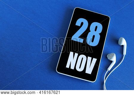 November 28. 28 St Day Of The Month, Calendar Date. Smartphone And White Headphones On A Blue Backgr