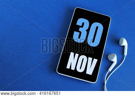 November 30. 30 St Day Of The Month, Calendar Date. Smartphone And White Headphones On A Blue Backgr