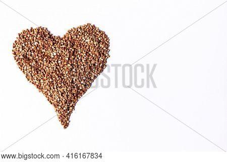 Buckwheat grain heap in heart shape on white background. Food ingredient.Top view.