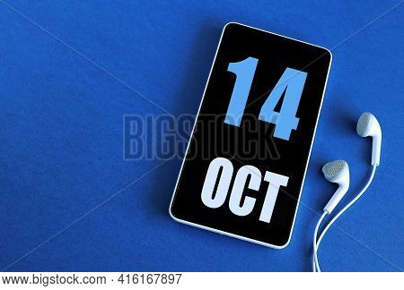 October 14. 14 St Day Of The Month, Calendar Date. Smartphone And White Headphones On A Blue Backgro