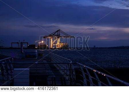 Night Promenade By The Sea Overlooking The Illuminated Cranes In The Port. Landscape View Of The Nig