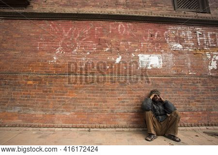 Kathmandu, Nepal, April 22: Unidentified Tired And Poor Young Man Resting In Front Of A House Outsid