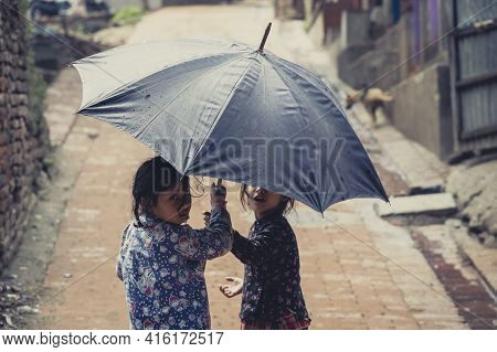 Bhaktapur, Nepal, April 24: Two  Nepalese Kids Playing With Umbrella In The Street Of Bhaktapur. Nep