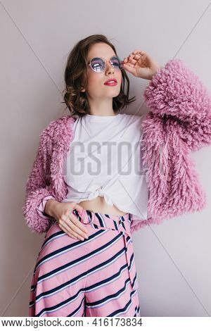 Carefree Young Lady With Brunette Hair Dreamy Posing In Trendy Outfit. Indoor Photo Of Curly Magnifi