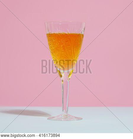 Crystal Glass Of Orange Tangerine Juice On Minimal Trendy Pink And Blue Background. Fresh Natural Ta