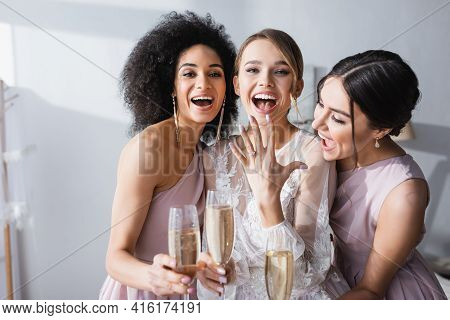 Excited Woman Showing Wedding Ring Near Interracial Bridesmaids With Champagne Glasses.