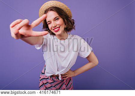 Blissful European Girl With Dark Eyes Posing In Trendy Straw Hat. Indoor Photo Of Sensual Female Mod