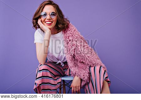 Ecstatic Short-haired Woman In Blue Glasses Sitting On Chair In Studio. Indoor Photo Of Pretty Europ