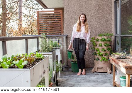 A Young Blonde Woman Is Planting A Vertical Tower Garden With Herbs And Vegetables On Her Urban Apar