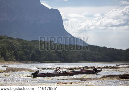 Canaima, Venezuela, April 10: Group Of Fishers Men Pushing A Wooden Traditional Boat In The River Of