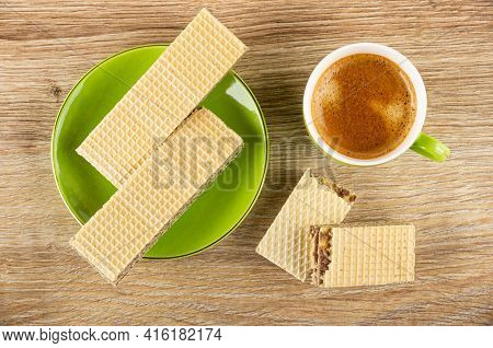 Wafers In Green Saucer, Pieces Of Broken Wafer, Coffee Espresso In Cup On Brown Wooden Table. Top Vi