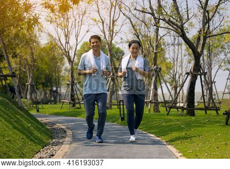 Smiling Senior Couple Jogging , Senior Couple Jogging And Running In The Park Outdoors Nature