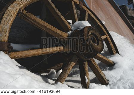 A Wooden Wheel From A Cart, Carriage Or Carriage Stands In The Snow In Winter