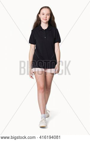 Teenage girl in black polo t-shirt for sporty youth fashion shoot full body