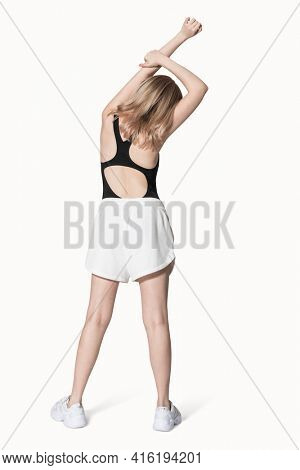 Blonde girl in black tank top and shorts activewear photoshoot full body